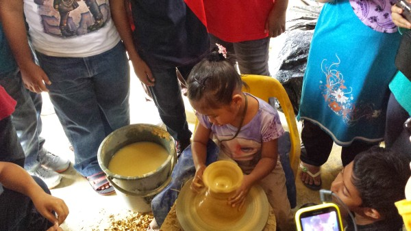 Kids having fun trying their hand at making labu sayong - traditional clay water pitchers.