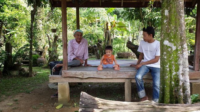 Baby Noah chillin' under a shelter under the watchful eye of the village elder on the left