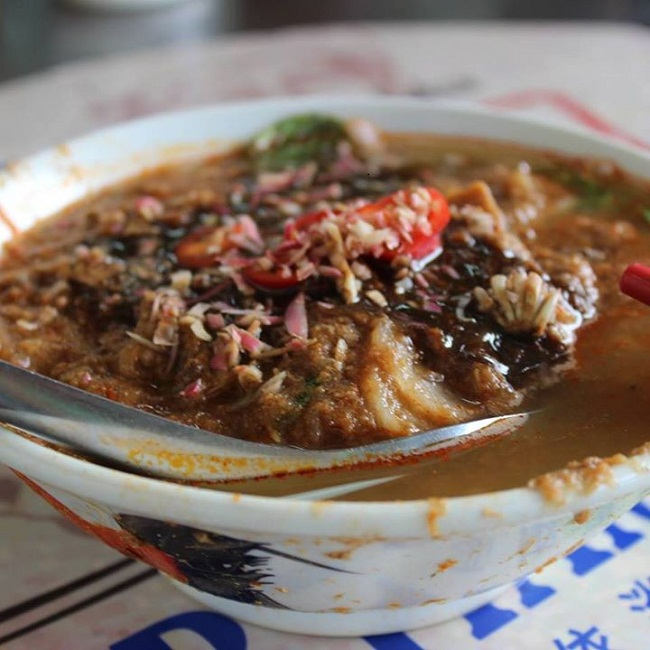 Asam Laksa presented in true street food style from Asam Laksa Air Itam, Penang.